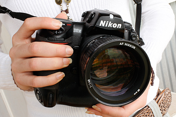 Close up of womans hand holdiing a DSLR Camera. Internet camera reviews, Excitations Photo Adventures