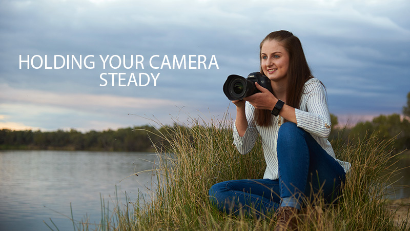 Young woman holding her camera looking out ofver Murray River. Prom image for Excitations Photo Adventures youtube tips and tricks.