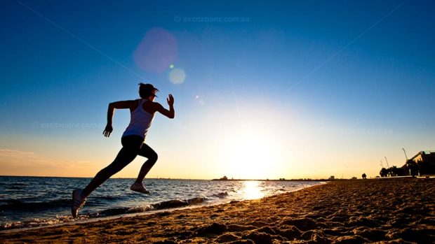 stock photo from excitations.com.au young woman running on beach at sunset.