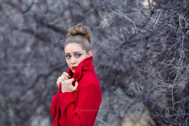 Beautiful young woman wearing a red coat against a subdued Winter background. Excitations Photo Adventures, Photo training online and workshops, regional and remote Australia.